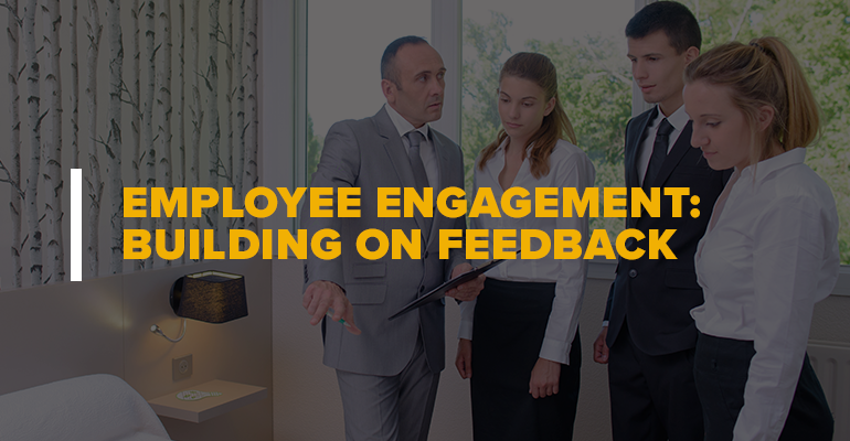 Hotel Manager and Workers With Text: Employee Engagement Building on Feedback