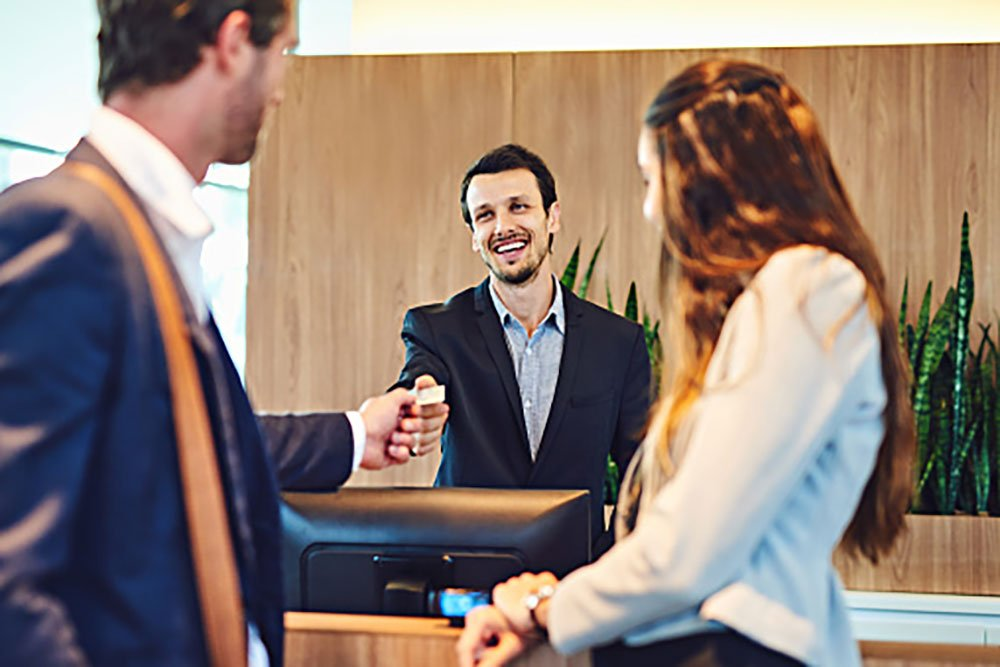 Front Desk Hotel Management Staff Greeting Couple Checking In