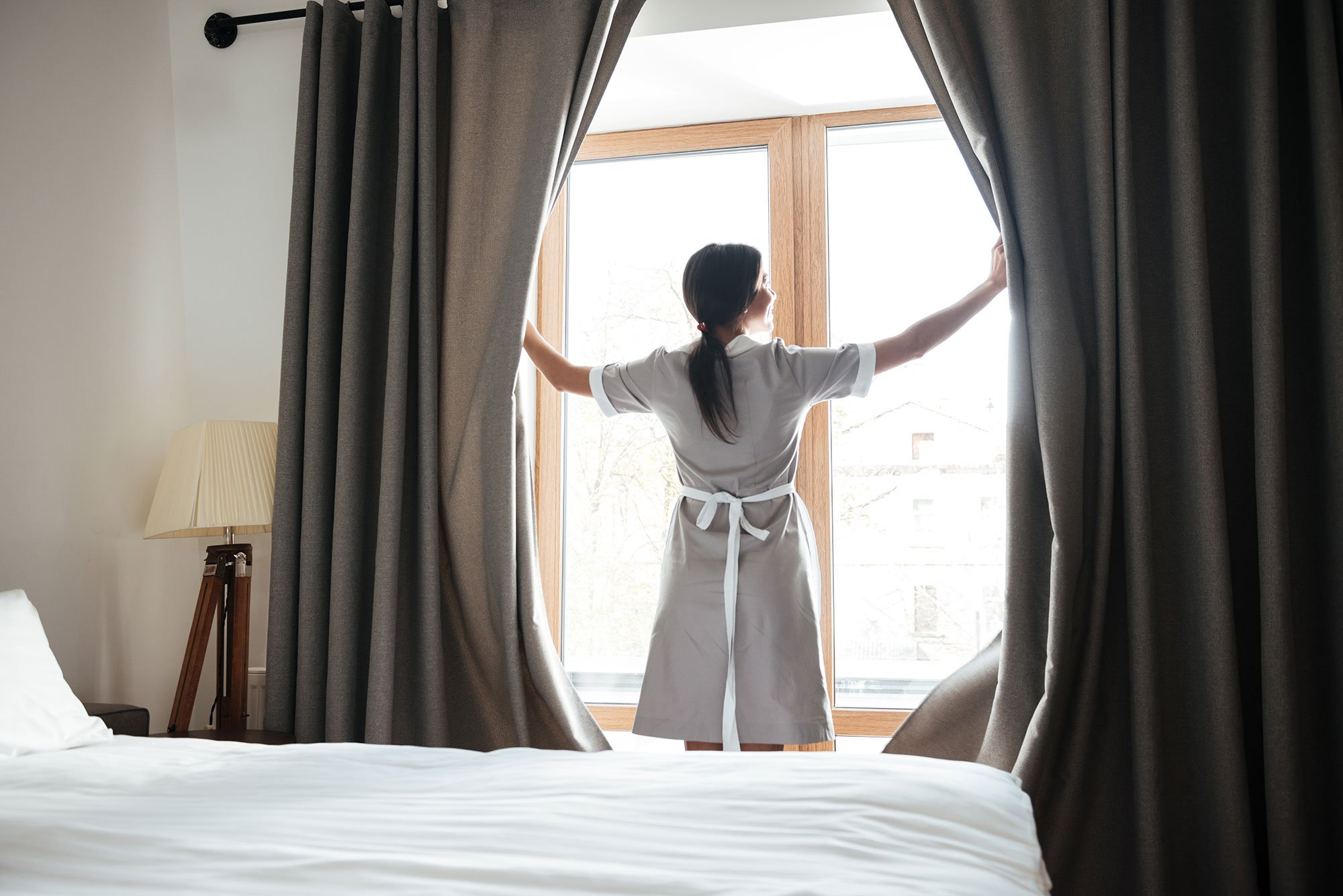 female-chambermaid-opening-window-curtains-in-the--PEY44UY_sm